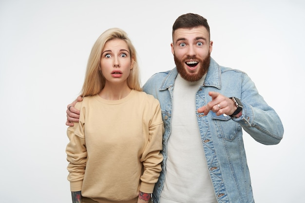 Indoor portrait of young blue-eyed pretty couple with shocked faces while standing on white, wearing beige sweatshirt and jeans coat