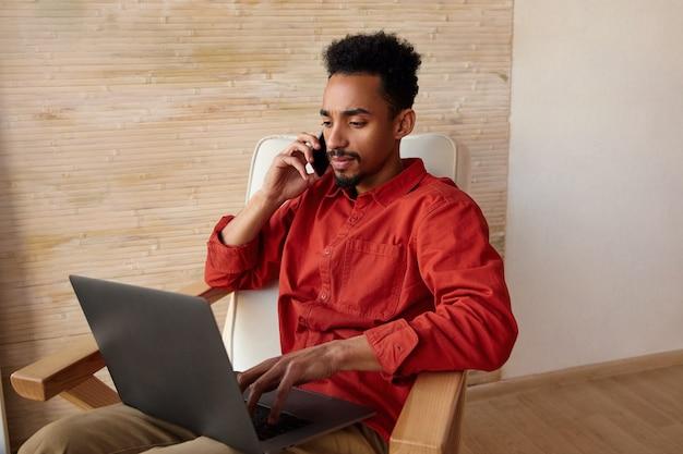 Ritratto dell'interno di giovane uomo d'affari dalla pelle scura con capelli ricci corti che aggrotta le sopracciglia durante la conversazione telefonica e guarda attentamente sullo schermo del suo laptop, isolato sull'interno della casa