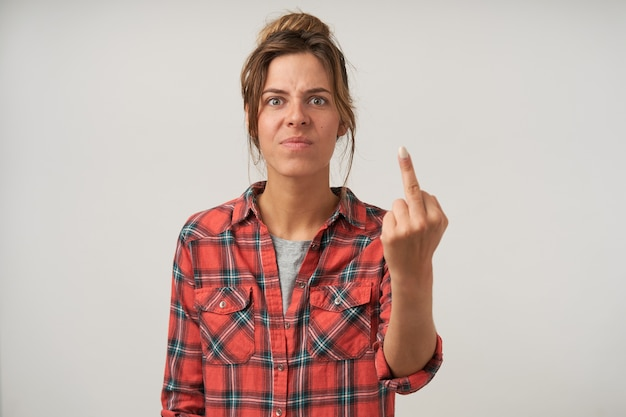 Indoor portrait of young disappointed female showing middle finger with raised hand, standing on white in casual wear, frowning with pout