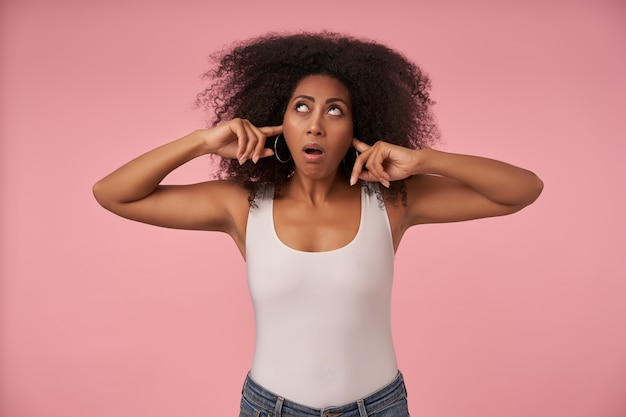 Indoor portrait of young dissatisfied dark skinned lady looking upwards and inserting index fingers into her ears to avoid annoying sounds, white shirt and jeans casual on pink