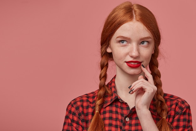 Indoor portrait of young ginger female looks thoughtfully at copy space while touching her cheek with a finger.