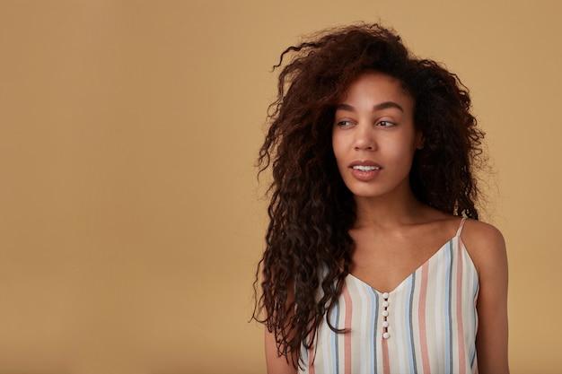 Ritratto dell'interno di giovane signora dalla pelle scura riccia dai capelli castani adorabile vestita di camicetta estiva straped guardando minuziosamente da parte con un sorriso leggero, isolato su beige