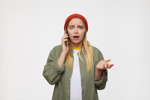 Ritratto dell'interno di giovane donna bionda graziosa con capelli lunghi che sollevano confusamente il suo palmo e guardando con stupore durante la conversazione telefonica, posa sul blu