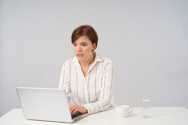 Ritratto interno di giovane donna dai capelli castani piuttosto con trucco naturale che arrotonda gli occhi e mostra i denti mentre guarda lo schermo del laptop con smorfia confusa, isolato su bianco