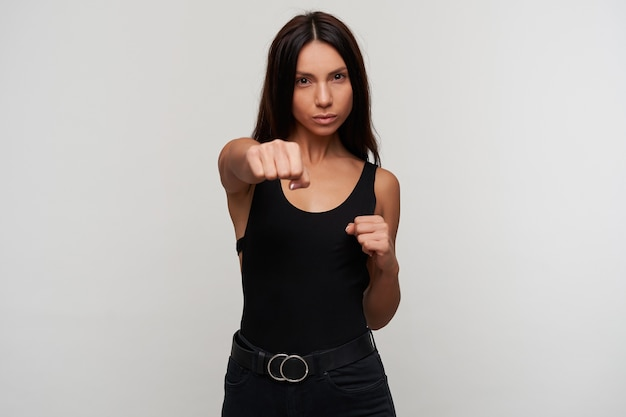 Indoor portrait of young pretty dark haired woman with casual makeup boxing with raised fists and looking menacingly, standing against white