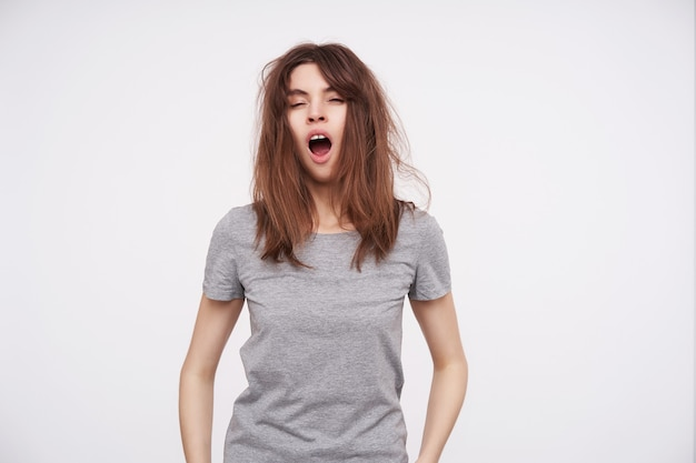 Indoor portrait of young pretty tired brown haired woman with wild hair closing her eyes while yawning with wide mouth opened, isolated on white
