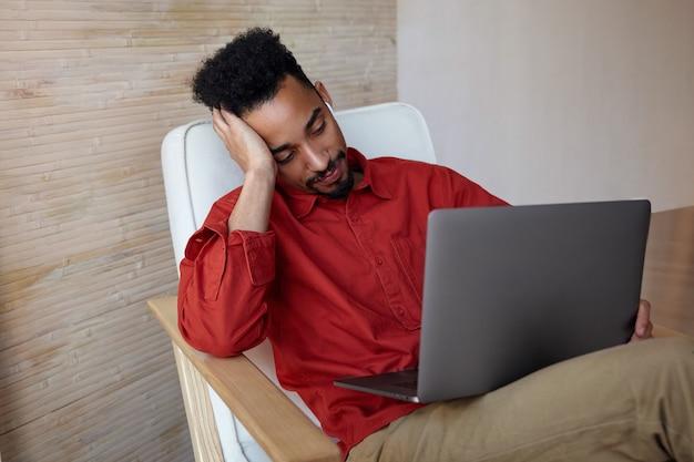 Ritratto dell'interno di giovane maschio scuro dai capelli corti che si siede nella sedia sull'interno domestico e che tiene il laptop sulle sue ginocchia, appoggiando la testa sulla mano sollevata mentre guarda noiosamente allo schermo