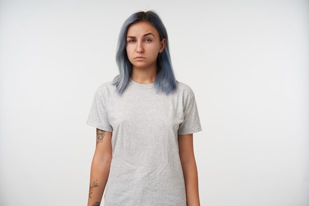 Indoor portrait of young tattooed lady squinting her eyes while looking suspiciously and keeping her hands along body while posing on white