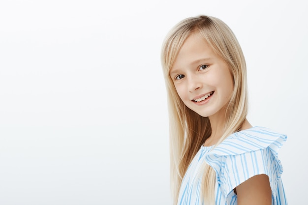 Indoor profile portrait of charming caucasian fair-haired young girl in trendy blue blouse, smiling broadly and feeling happy after piano lesson, relaxing and playing with classmates over gray wall