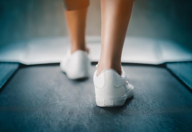 Ноги бегуна в помещении медленно идут по беговой дорожке для легких упражнений, закрытый выстрел.