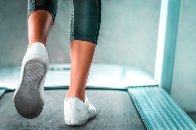 Indoor runner legs is walking slowly on the treadmill for light exercise closed up shot.