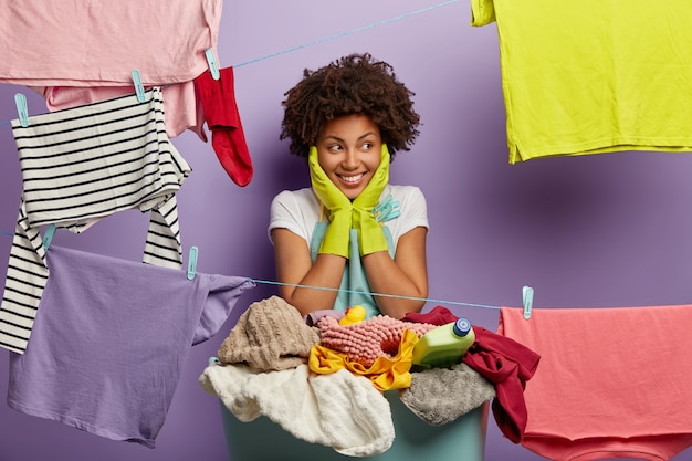 Indoor shof of cheerful dark skinned curly female touches both cheeks, wears apron and rubber gloves, stands near basin of laundry, hangs up clothes on rope with clothespins. housework concept