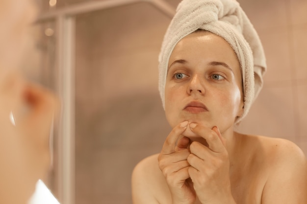 Indoor shoot of young adult beautiful woman wearing bath towel standing in bathroom and looking for or squeezing acne on chin, mirror reflection, beauty procedures.