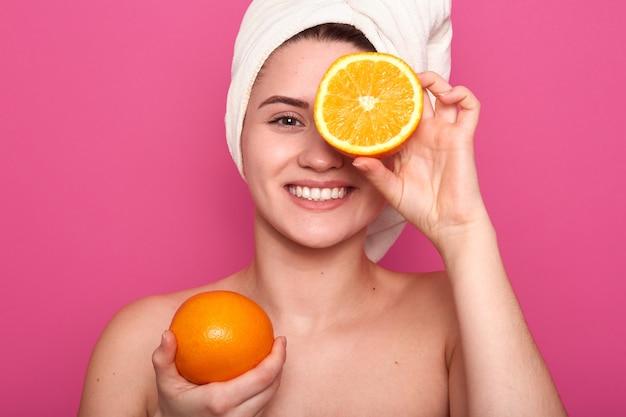 片方の手でオレンジ色を保持し、果物の半分で目を覆っている若い女性の屋内ショーツ