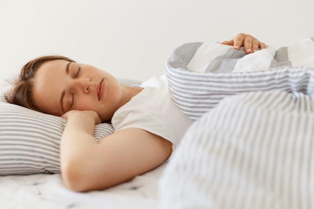 Corto al coperto su giovane e bella femmina addormentata adulta che indossa una maglietta casual bianca sdraiata a letto sotto la coperta con gli occhi chiusi, dorme la mattina del fine settimana.