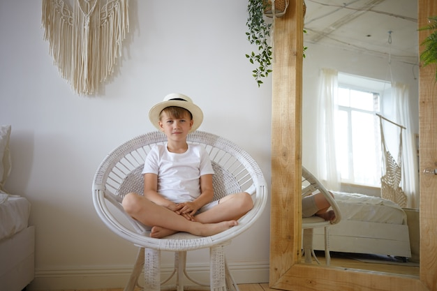 Indoor shot of 10 year old boy sitting in round armchair keeping legs crossed, looking and smiling at camera, wearing white t-shirt and summer hat. cute male kid posing in bedroom with large mirror