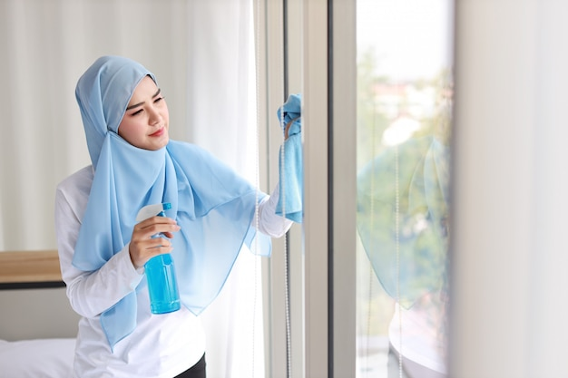 Indoor shot active young beautiful asian muslim housewife woman holding cleaning spray, washing window glass. portrait cute girl with happy emotional cleaning bedroom in new apartment after moved in.