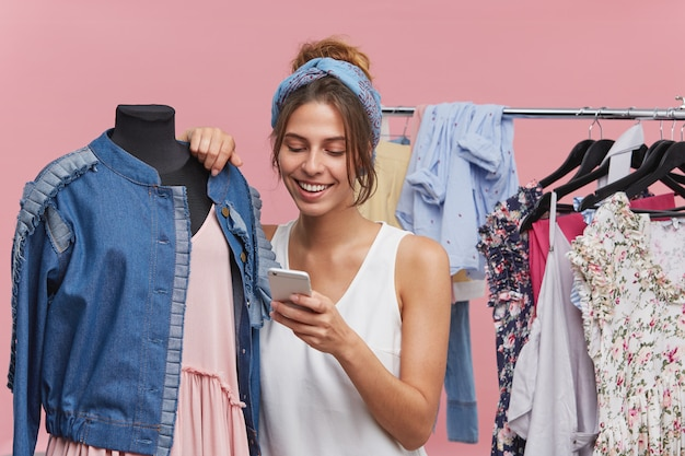 Indoor shot of adorable female buyer spending her free time in boutique, standing near dummy with clothes, reading news online while using free internet connection. shop assistant selling clothes