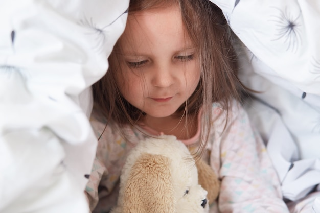 Indoor shot of adorable little child girl playing with teddy bear in bed under blanket
