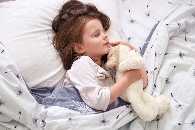 Indoor shot of adorable little child girl sleeping in bed with her toy, child girl hugging teddy bear while laying on linens with dandelion