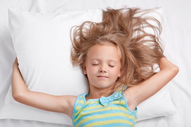 Indoor shot of adorable small female kid with uncombed light hair, keeps hands under soft pillow, dressed in pajamas, poses in comfortable bed alone. children, night rest and lifestyle concept