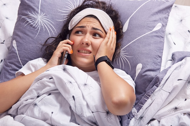 Indoor shot of adorable young woman having conversation with friend or boyfriend, keeps hand on cheek, looking away, wearing t shirt and blindfold on forehead, lying on pillow in bed, under blanket.