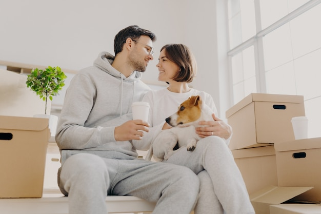 Indoor shot of affectionate woman and man express love to each other, have good relationship, drink coffee, pose with favourite pet, have to unpack many cardboard boxes, bought new apartment
