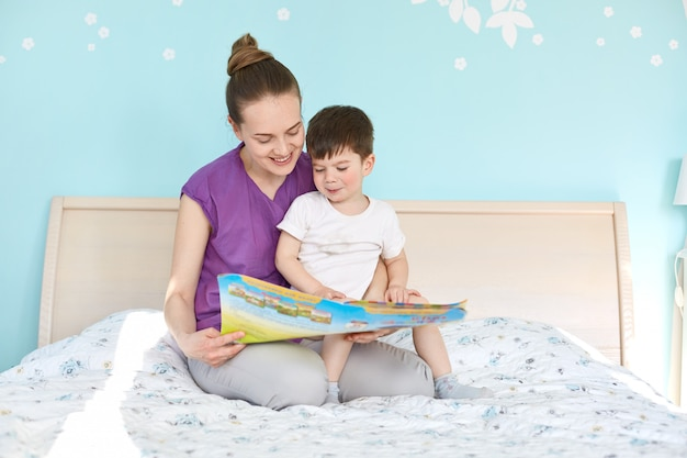 Indoor shot of affectionate woman and small boy read interesting story from book