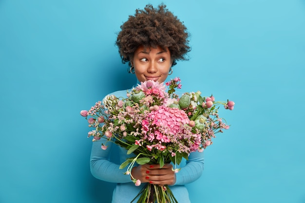 Indoor shot of afro american woman receives beautiful flowers enjoys romantic date looks with dreamy pensive expression aside gets bouquet from secret admirer or lover isolated on blue studio wall