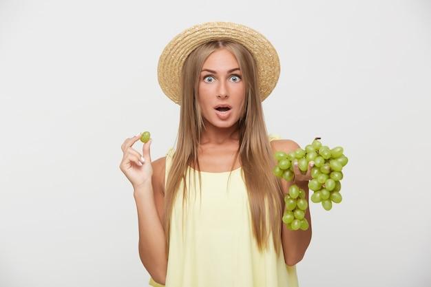 Tiro al coperto di stupito giovane signora bionda dai capelli lunghi nel cappello di paglia che guarda l'obbiettivo con gli occhi spalancati e la bocca aperta, in piedi su sfondo bianco con grappolo d'uva