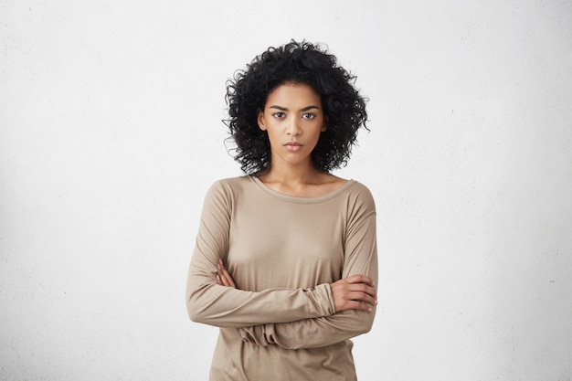 Indoor shot of angry grumpy young mixed race female dressed casually keeping arms folded, looking with strict and skeptical expression