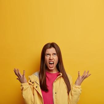 Tiro al coperto di donna arrabbiata e indignata guarda con irritazione sopra, infastidita dai vicini rumorosi, alza i palmi e urla ad alta voce