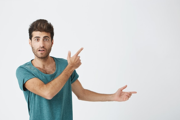 Indoor shot of astonished good-looking man dressed in casual cloth having excited fascinated look, indicating at blank  wall with his index finger. isolated shot, horizontal