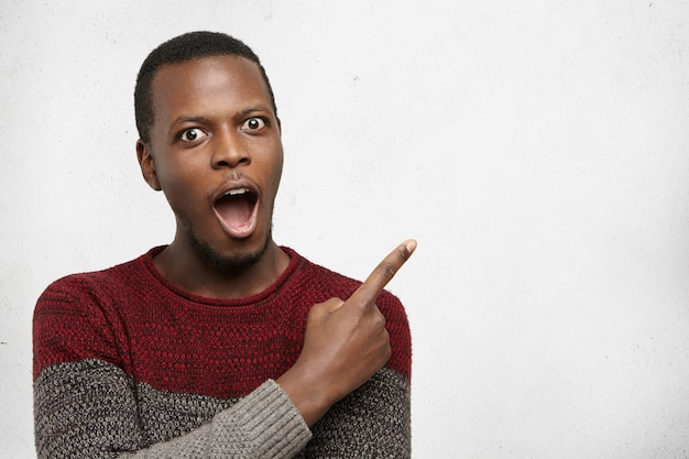 Indoor shot of astonished young dark-skinned man dressed in casual sweater having excited fascinated look, pointing index finger