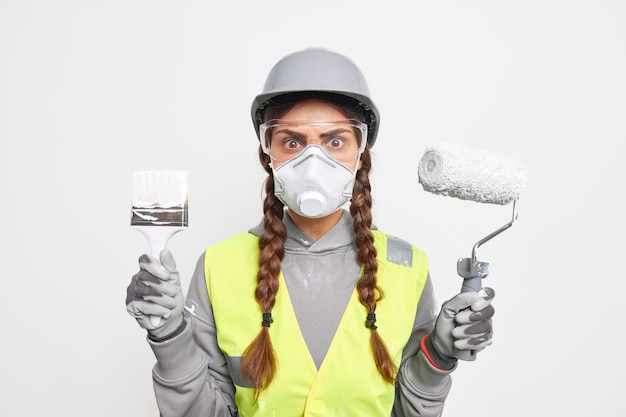 Indoor shot of attentive busy woman builder with pigtails looks stunned through transparent safety glasses holds paint brush and roller involvd in reconstruction wears protective helmet and face mask