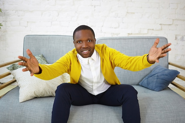 Indoor shot of attractive adult dark skinned man sitting on couch in living room and gesturing emotionally, keeping hands wide while watching football game on tv, supporting his favorite team