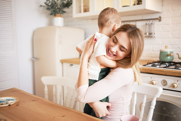 Indoor shot of attractive blonde young mother spending nice time at home embracing toddler child sitting at dining table in cozy kitchen, smiling, enjoying happy sweet moments of her motherhood
