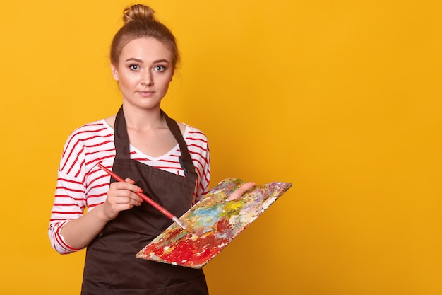 Indoor shot of attractive blue eyed young painter standing isolated over yellow