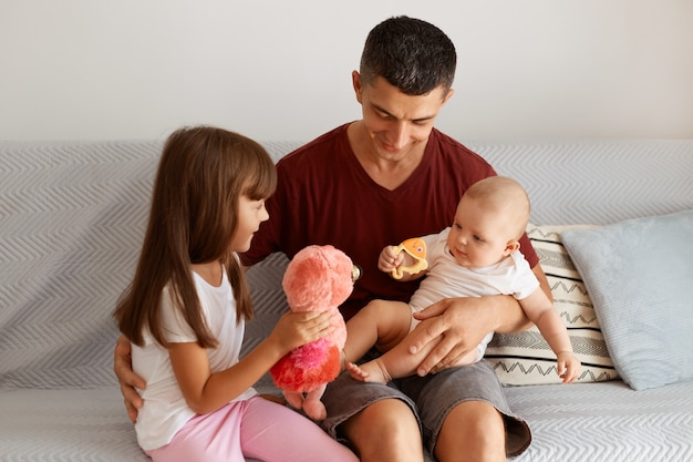 Indoor shot of attractive brunette man wearing maroon t shirt spending time with his children, sitting on sofa in light room, playing together, expressing happiness.