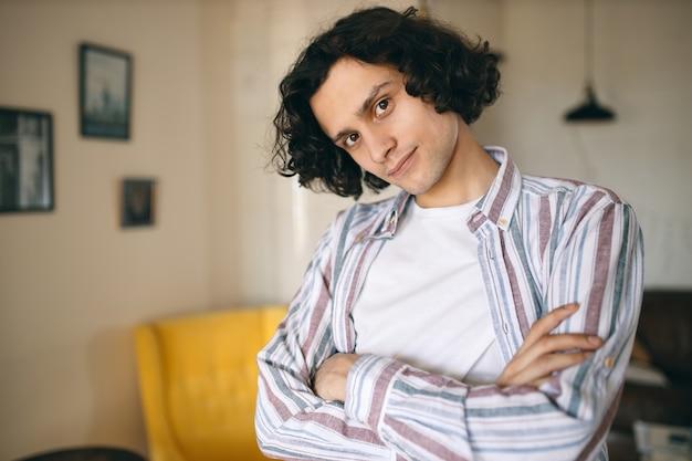 Tiro al coperto di attraente giovane uomo caucasico fiducioso con i capelli ricci in posa nell'elegante salotto interno, tenendo le braccia incrociate sul petto, sentendosi al sicuro mentre si è a casa.