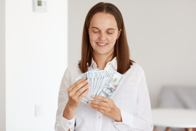 Indoor shot of attractive dark haired female wearing white casual style shirt, holding fan of money in hands, counting banknotes with happy facial expression.
