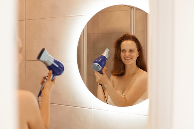Indoor shot of attractive dark haired woman drying hair in bathroom with hair dryer, looking at reflection in the mirror, doing morning procedures before going to work.