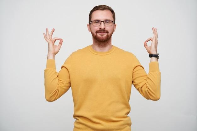 Tiro al coperto di attraente giovane uomo barbuto in bicchieri con capelli corti castani dita pieghevoli in segno mudra mentre posa, guardando positivamente con faccia calma