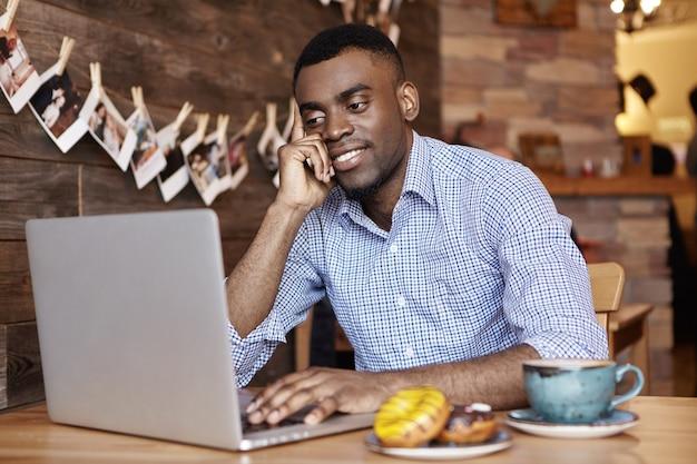 Indoor shot of attractive young dark-skinned employee in shirt using generic laptop computer
