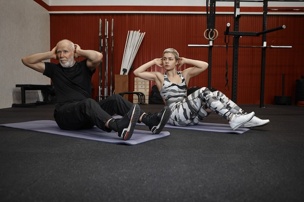 Indoor shot of attractive young female fitness coach in khaki sportswear and athletic unshaven elderly male exercising together in gym, doing twisting crunches, working on abdominal muscles