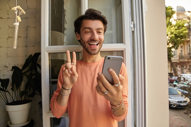 Indoor shot of attractive young man with beard leaning on opened window while having videochat with his friends, smiling cheerfully and showing peace gesture