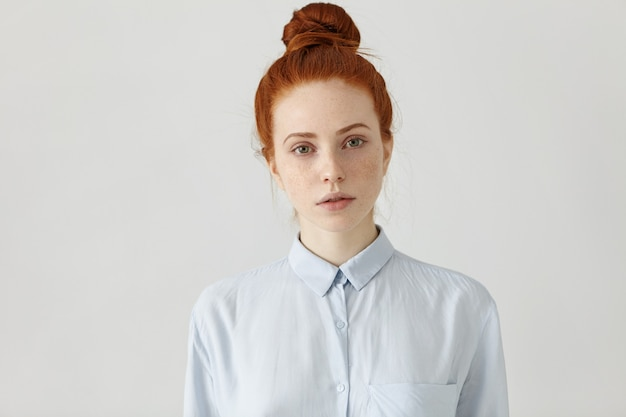 Indoor shot of attractive young redhead freckled caucasian office worker with hair bun