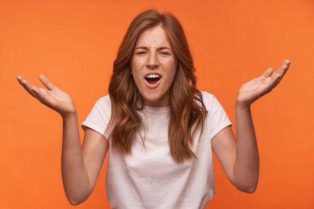 Tiro al coperto di attraente giovane donna con acconciatura casual che alza i palmi verso l'alto, guardando con la bocca larga aperta e accigliata, isolata