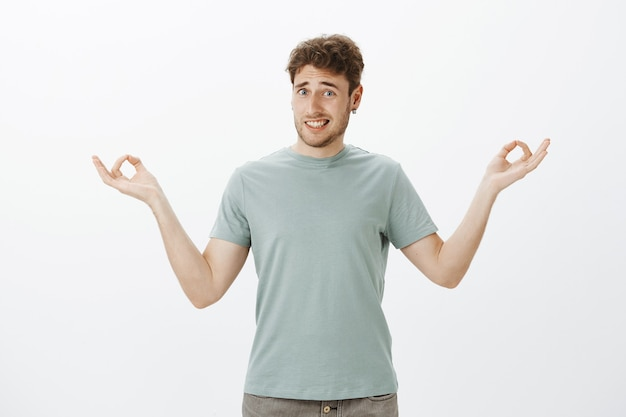 Indoor shot of awkward unsure funny guy with bristle in earrings, smiling clumsy while standing with spread hands in zen gesture and being clueless how meditate or do yoga