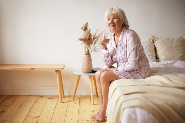 Indoor shot of barefooted attractive gray haired female pensioner sitting on bed with feet on wooden floor, holding glass, drinking fresh water in morning. people, lifestyle, bedtime and aging concept